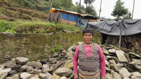 A-Nepalese-woman-stands-in-front-of-a-makeshift-tent-home-after-becoming-homeless-during-the-devastating-earthquake-there