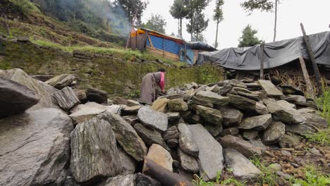 A-Nepalese-woman-piles-rocks-in-front-of-a-makeshift-tent-home-after-becoming-homeless-during-the-devastating-earthquake-there