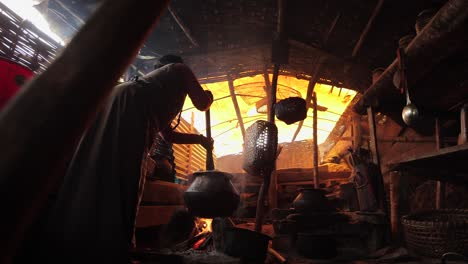 A-woman-cooks-over-an-open-fire-inside-her-home-in-Tibet-or-Nepal