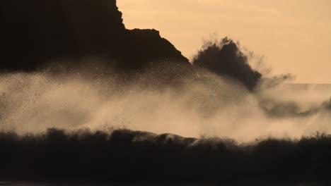 Massive-waves-break-against-a-rocky-shore-in-golden-light-in-slow-motion
