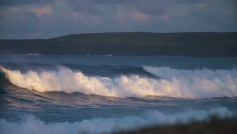 Ocean-waves-roll-into-a-coastline-in-golden-light-in-slow-motion