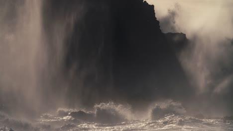 Huge-ocean-waves-roll-into-a-rocky-shore-in-slow-motion
