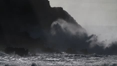 Huge-ocean-waves-roll-and-crash-into-a-rocky-shore-in-slow-motion