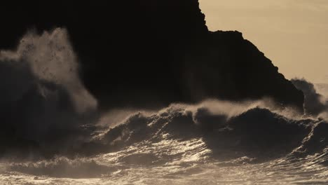 Huge-ocean-waves-roll-and-crash-into-a-rocky-shore-in-slow-motion-1