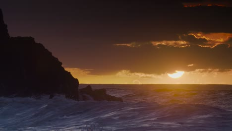 The-sun-sets-as-ocean-waves-break-against-Hawaiian-shores