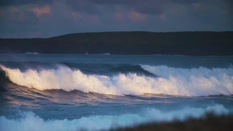 Waves-crash-against-a-rocky-shore-in-golden-light