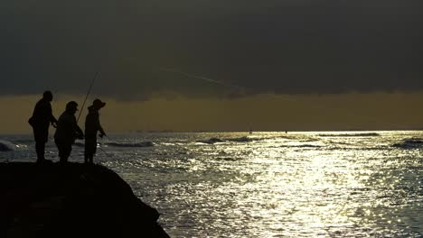 Three-Fishermen-cast-during-sunset-at-Ala-Moana-Beach-Park-in-Honolulu-Hawaii