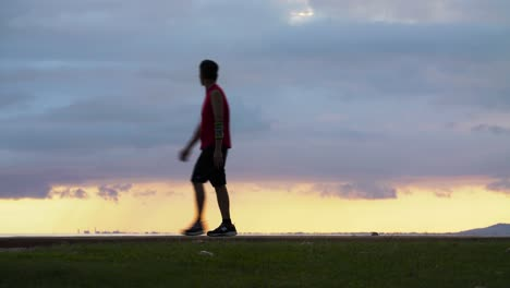 Man-walks-through-frame-as-he-watches-sunset-scene-at-Ala-Moana-Beach-Park-in-Honolulu-Hawaii
