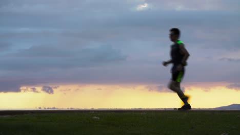 Man-runs-through-frame-sunset-scene-at-Ala-Moana-Beach-Park-in-Honolulu-Hawaii