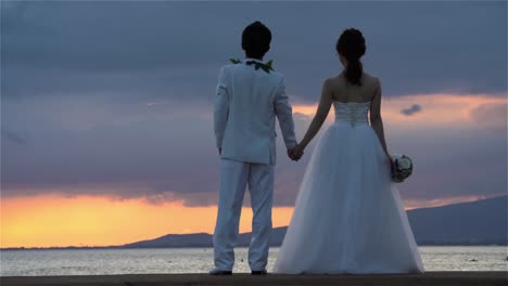 Wedding-couple-watches-sunset-scene-at-Ala-Moana-Beach-Park-in-Honolulu-Hawaii