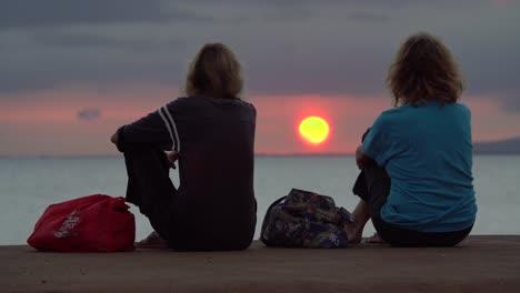 Two-women-watch-sunset-at-Ala-Moana-Beach-Park-in-Honolulu-Hawaii