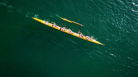 Beautiful-aerial-over-an-outrigger-canoe-paddled-on-blue-water-1