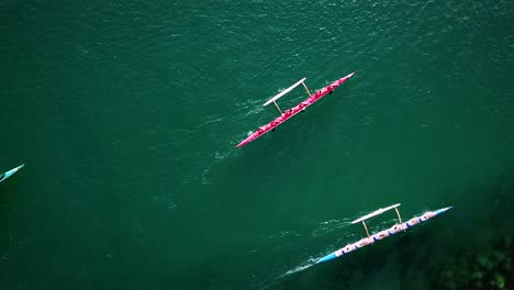 Beautiful-aerial-over-a-red-outrigger-canoe-paddled-on-blue-water