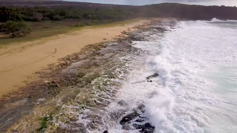 Aerial-over-a-couple-dancing-and-playing-on-a-long-beach-in-Molokai-Hawaii