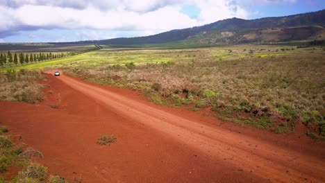 A-silver-Jeep-drives-fast-along-a-red-dirt-road-on-the-island-of-Lanai-in-Hawaii