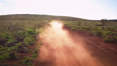 A-silver-Jeep-drives-fast-along-a-red-dirt-road-on-the-island-of-Lanai-in-Hawaii-1