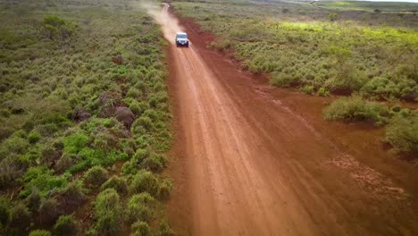 A-silver-Jeep-drives-fast-along-a-red-dirt-road-on-the-island-of-Lanai-in-Hawaii-2