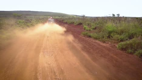 A-silver-Jeep-drives-along-a-red-dirt-road-on-the-island-of-Lanai-in-Hawaii