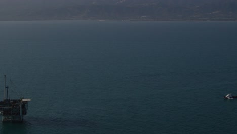 An-vista-aérea-shot-over-a-boat-heading-out-to-oil-derricks-and-platforms-in-the-Santa-Barbara-Channel-California