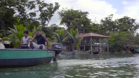 Vista-Desde-Un-Barco-De-Una-Cabaña-De-Pueblo-Sobre-Pilotes-A-Lo-Largo-De-Un-Río-En-Guatemala-1