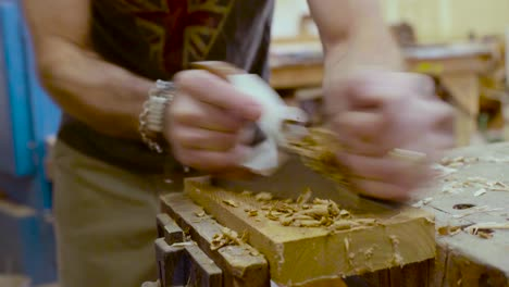 A-woodworker-works-cutting-wood-in-his-studio-1
