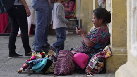 Una-Mujer-Guatemalteca-Mira-Su-Teléfono-Celular-En-Una-Calle-Muy-Transitada