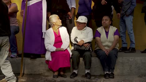 Colorful-looking-people-sit-on-the-sidewalk-in-Antigua-Guatemela-during-Easter-celebrations