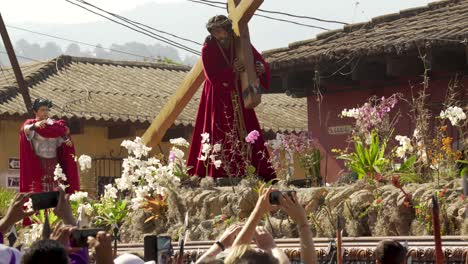 Women-carry-giant-statues-of-Jesus-and-the-cross-in-a-colorful-Christian-Easter-celebration-in-Antigua-Guatemala