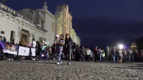 Pov-Aufnahme-Von-Menschen-Die-Nachts-Entlang-Einer-Belebten-Straße-Vor-Der-Kathedrale-In-Antigua-Guatemala-Gehen-