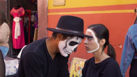 A-man-paints-a-woman-s-face-for-the-day-of-the-dead-in-San-Miguel-De-Allende-Mexico