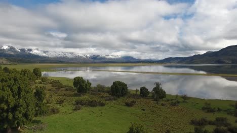 Beautiful-aerial-of-Andes-mountains-a-lake-and-pasture-land-near-Los-Alerces-National-Park