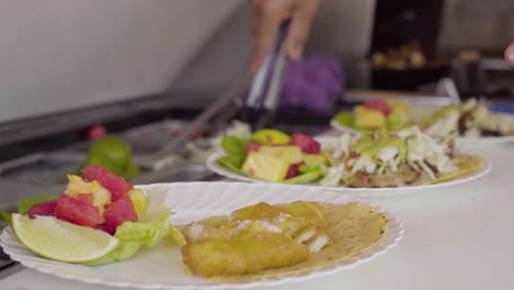 A-short-order-chef-prepares-fish-tacos-in-a-restaurant-kitchen
