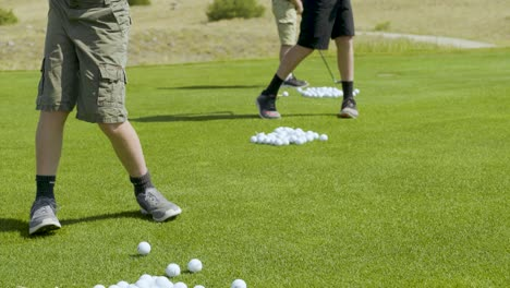 Three-young-golfers-hitting-a-bucket-of-balls-at-the-Rock-Creek-Cattle-Co-driving-range
