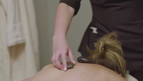 A-masseuse-uses-heated-stones-during-the-massage-of-a-female-client