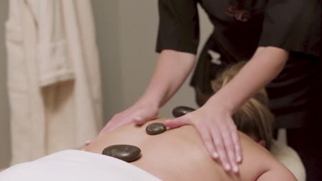 A-masseuse-uses-heated-stones-during-the-massage-of-a-female-client-1