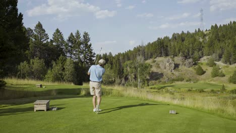 A-male-golfer-hits-a-short-iron-off-a-par-three-hole-at-an-exclusive-course-in-Montana