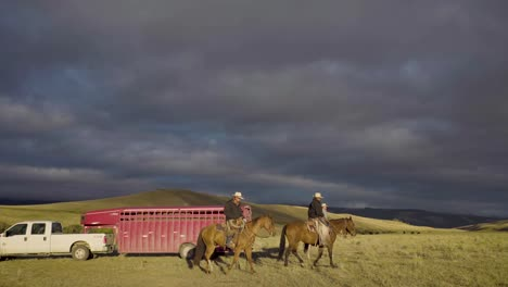 Cowboys-on-horseback-during-an-early-morning-roundup-of-a-herd-of-cattle-in-Montana
