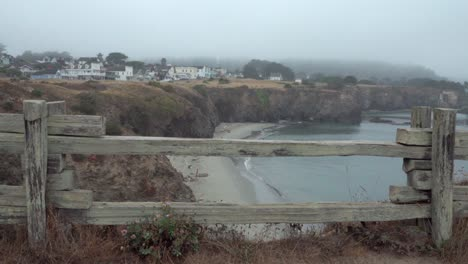 A-wooden-fence-frames-a-foggy-morning-view-of-small-beach-and-the-historic-wooden-buildings-of-Mendicino-California