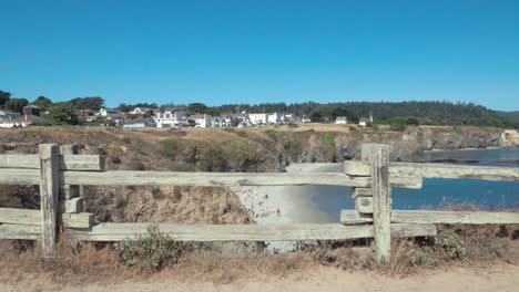 Beautiful-dolly-shot-wooden-fence-frames-a-blue-sky-day-view-of-a-small-beach-and-historic-buildings-Mendicino-CA