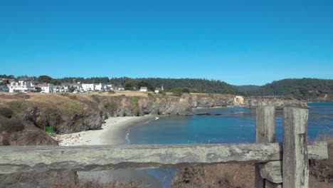 Beautiful-dolly-shot-wooden-fence-frames-a-blue-sky-day-view-of-a-small-beach-and-historic-buildings-Mendicino-CA-3
