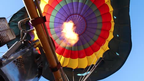 Flames-from-a-burner-heat-the-air-keeping-a-brightly-colored-hot-air-balloon-aloft-on-a-sunny-California-morning