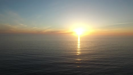 A-beautiful-aerial-above-a-golden-sunset-over-a-generic-ocean-coast