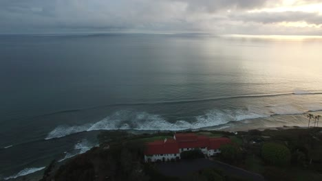 A-beautiful-aerial-above-waves-rolling-into-the-California-coastline-north-of-San-Diego-1