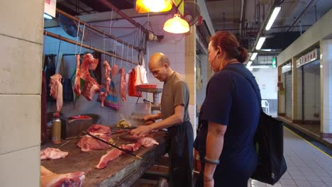 A-meat-seller-in-Hong-Kong-cuts-meat-with-a-knife-for-a-customer