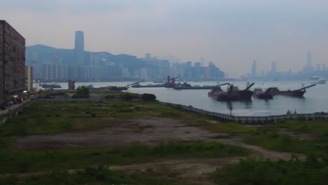 Pan-across-Hong-Kong-harbor-in-foggy-hazy-and-smoggy-conditions-with-barges-and-boats-foreground