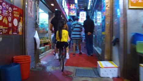 Following-shot-of-a-child-riding-on-a-bicycle-through-an-indoor-market-in-Hong-Kong