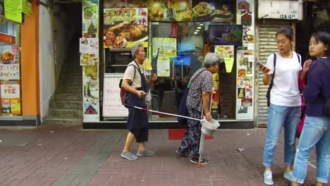 A-poor-handicapped-homeless-blind-man-musician-is-led-by-his-wife-down-a-street-in-Hong-Kong-China-1