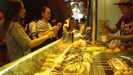 A-Chinese-woman-prepares-food-at-a-street-stall-in-Hong-Kong-China