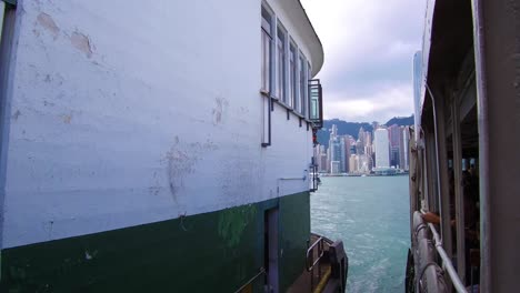 Establishing-shot-from-the-ferry-boat-reveals-Hong-Kong-harbor-and-skyline-with-clouds