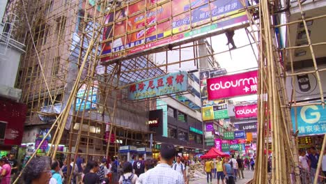 Pan-up-from-a-busy-commercial-district-in-Hong-Kong-China-to-reveal-workers-on-bamboo-scaffolding-1